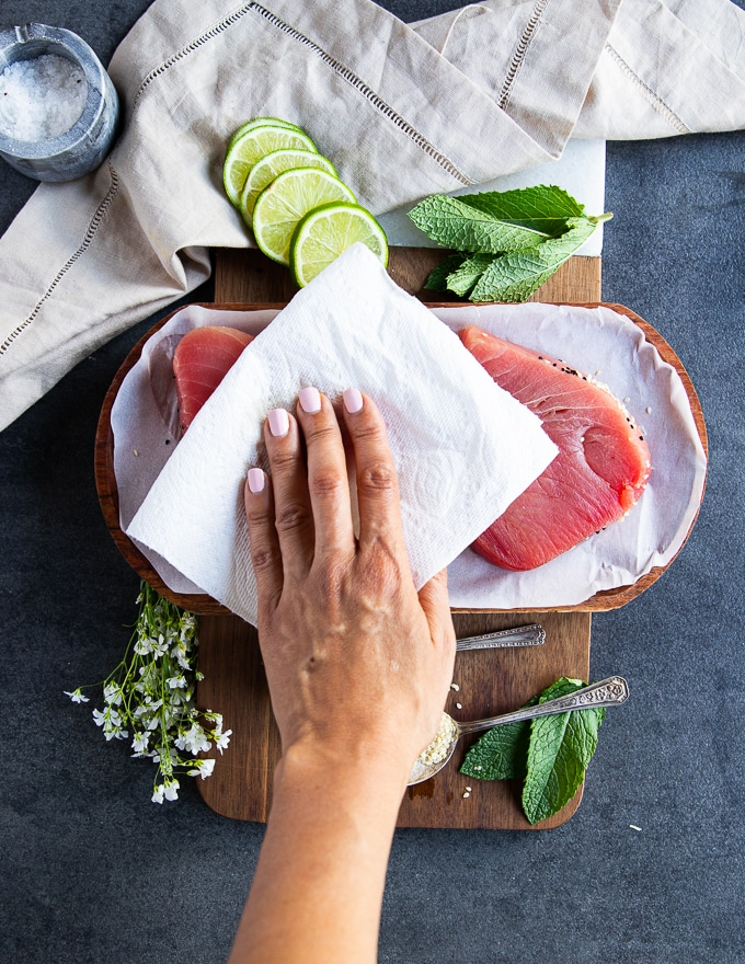 A hand holding a kitchen towel patting down the tuna steaks dry before seasoning