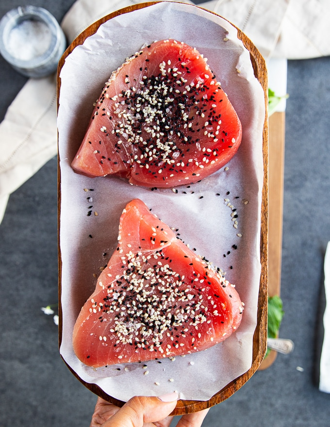 seasoned tuna steaks with sesame seeds and salt on a parchment paper ready to sear
