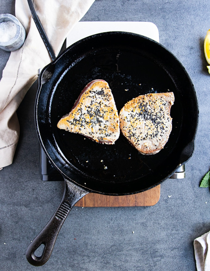 tuna steak recipe flipped in a cast iron pan after being golden on one side