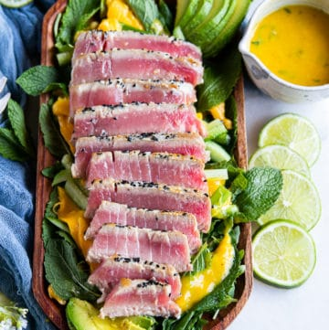 sliced tuna steak recipe on a bed of mint and greens surrounded by lime slices a tew towel and two salad spoons on a white marble