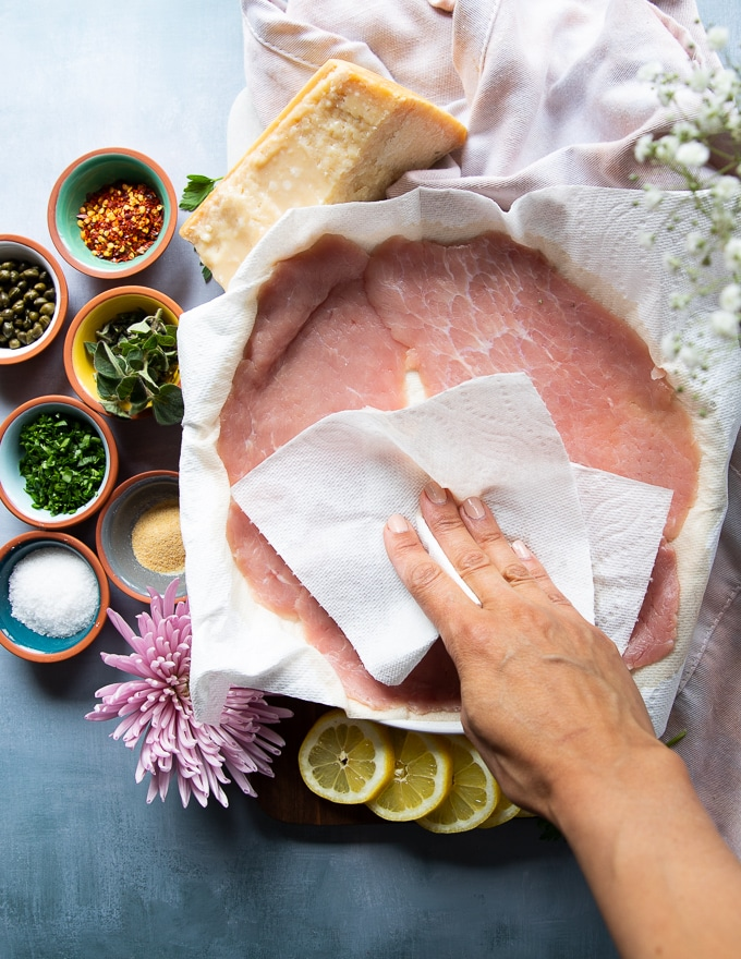 Thin slices of veal scallopini on a plate and a hand patting dry the veal using a paper towel