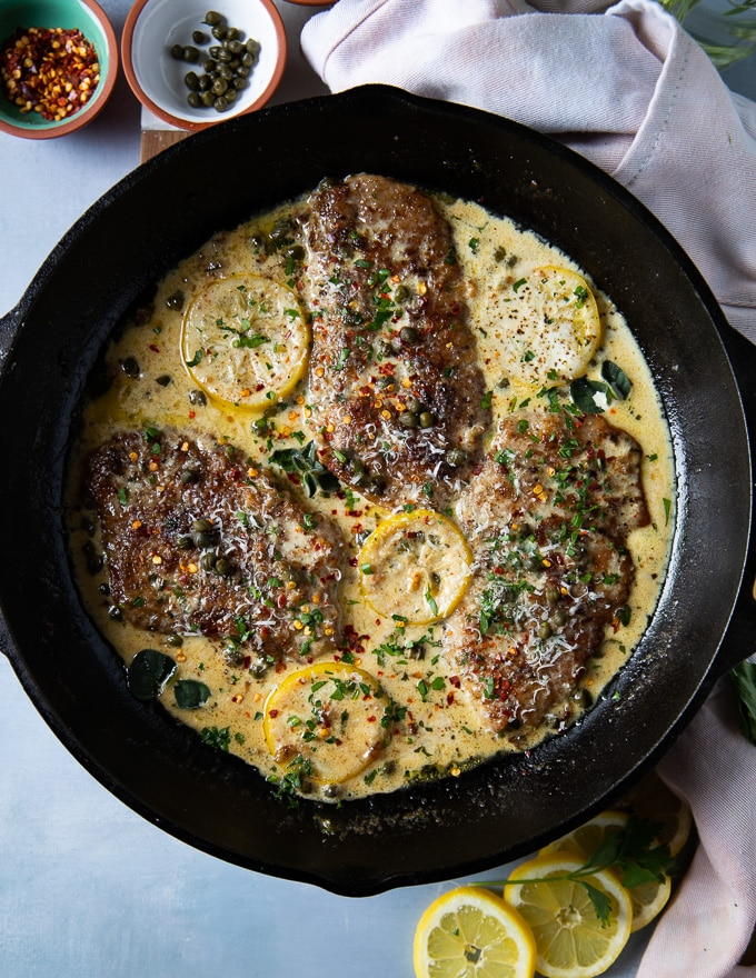 The finished veal scallopini in piccata sauce is ready and garnished with herbs and lemon slices