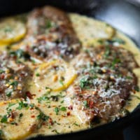 close up of one Veal Scallopini cooked in Piccata sauce in a black pot with lemon slices