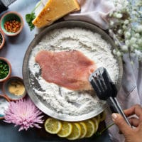 A hand holding a slice of veal scallopini using a tong and dredging it in the flour bowl