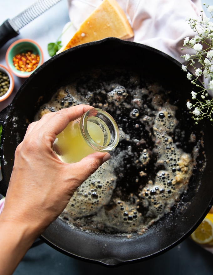melted butter and garlic cooking in the same cast iron pan and a hand pouring some lemon juice to make the piccata sauce