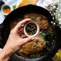 A hand adding in some capers to the piccata sauce