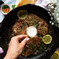 A hand finishing off the piccata sauce with a touch of cream in a small cup and the veal being added back to the pan