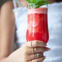 A hand holding a tall cup of watermelon slushie with a mint sprig on top