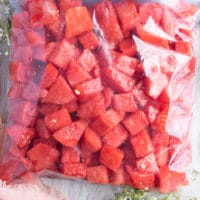 watermelon cubes placed in a ziploc bag and ready to freeze