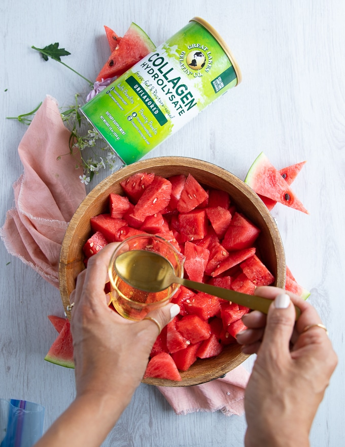 a lage bowl of cubed watermelon and a hand adding the simple syrup to the watermelon