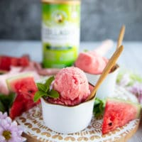 close up of one cup of watermelon sorbet with two scoops in a white bowl and a wooden spoon, and a garnish of mint