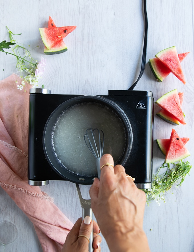 a hand using a whisk to whisk in all ingredients of the simple syrup in a pot until smooth.