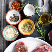 spice blend for NBY strip steak including small bowls of salt, pepper, onion flakes, dried rosemary and olive oil