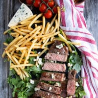 grilled NY strip steak on a board surrounded by fries, greens and a chunk of blue cheese