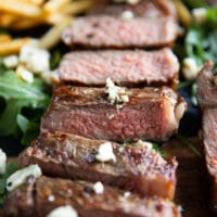 close up of a whole NY strip sliced up and topped with blue cheese crumbles