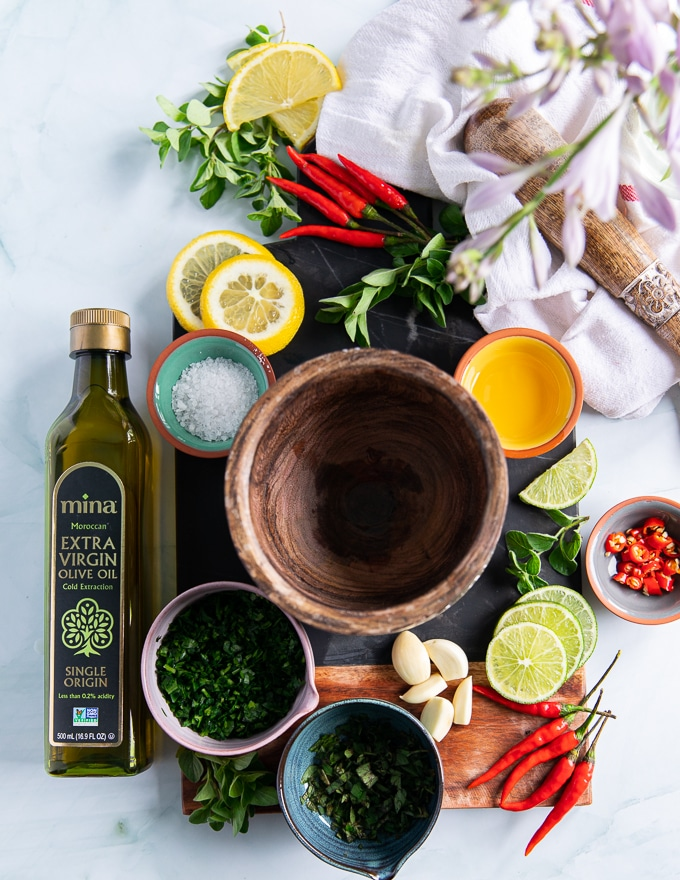 ingredients for chimichurri recipe on a board includes fresh garlic, fresh parsley, fresh oregano, salt, vinegar, lemon slices, red chillies and lots of olive oil