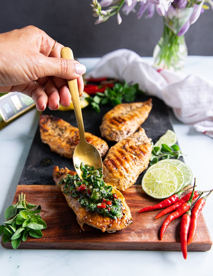 A hand drizzling a lot of chimichurri sauce over grilled chicken to finish off chicken chimichurri