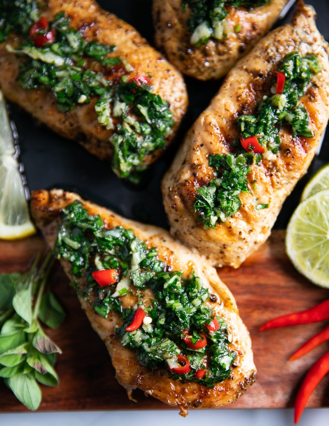 close up of three pieces of chicken chimichurri drenched with chimichurri sauce
