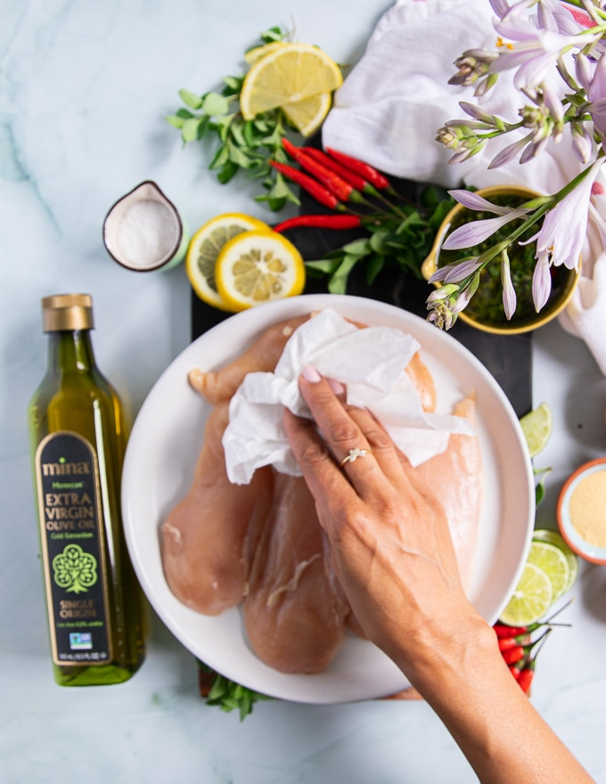 a hand patting down the chicken breasts before seasoning