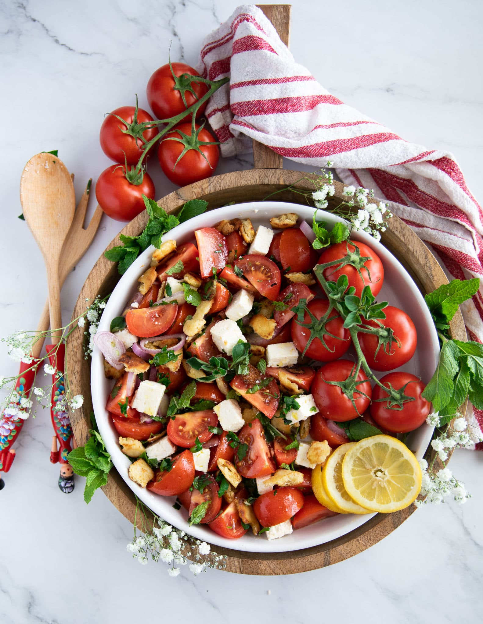 final plate of a tomato salad recipe surrounded by fresh tomatoes, herbs, lemon slices and a tea towel and two salad serving spoons