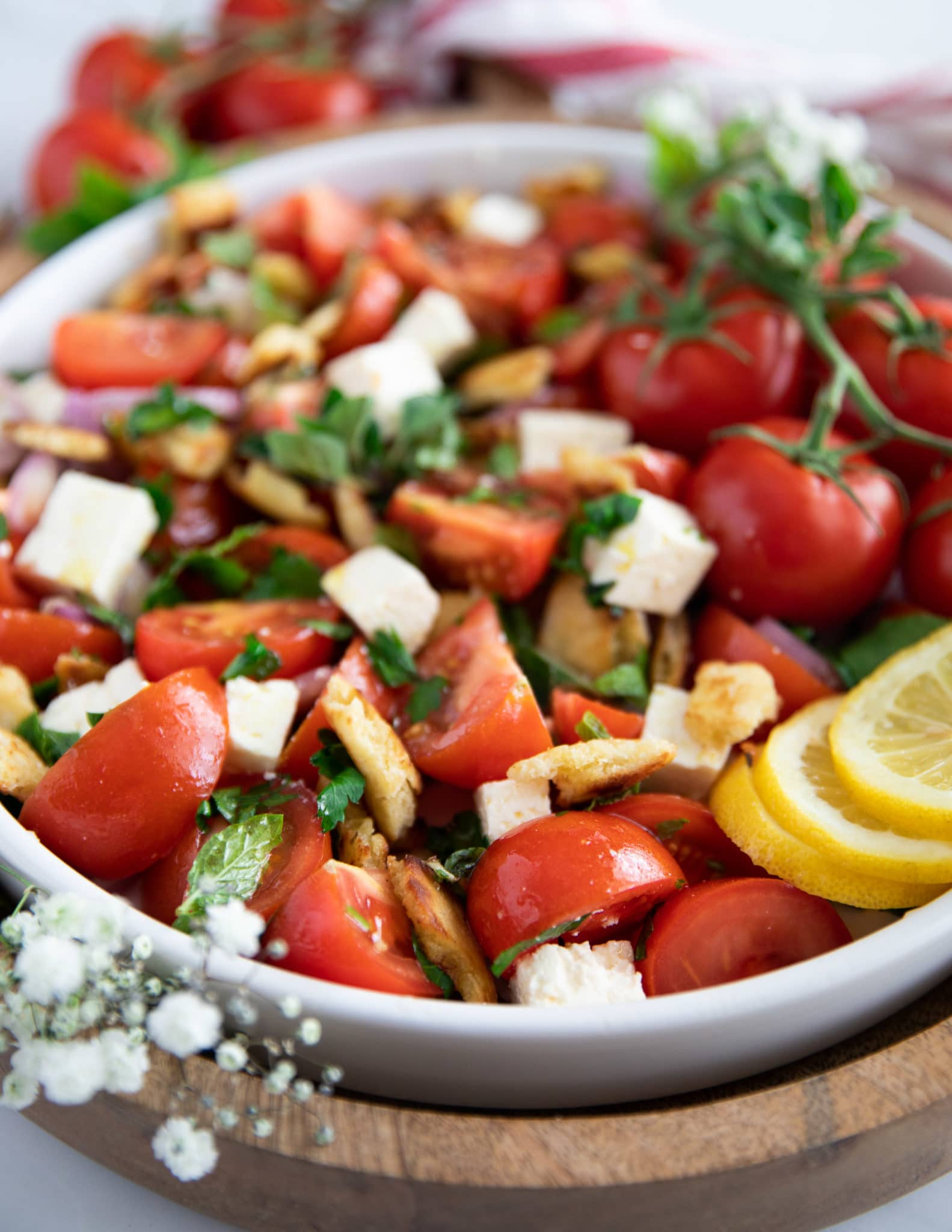 A plate of tomato salad showing the fresh herbs, feta and bread surrounded by lemon slices on a wooden board