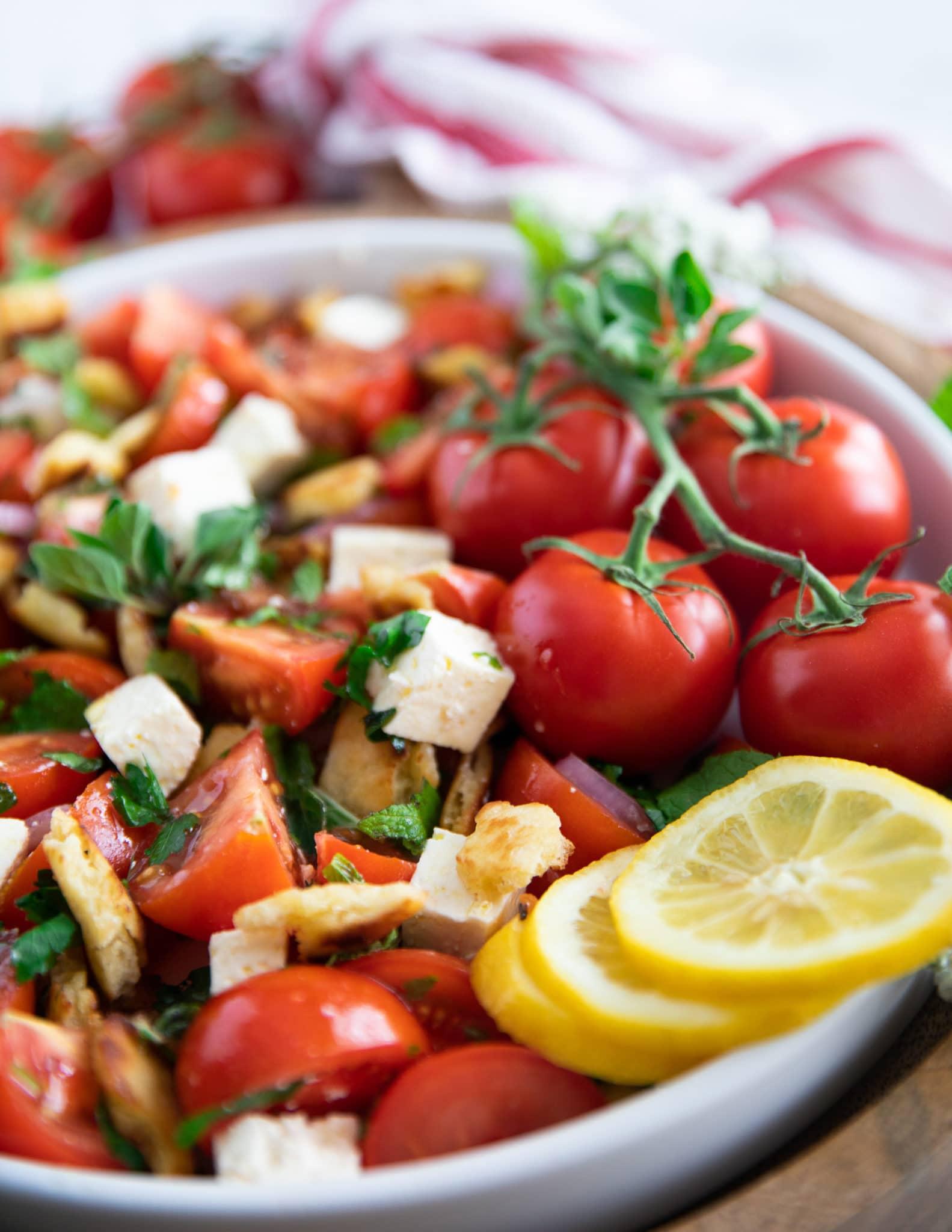 close up of a tomato salad showing the fresh mint, oregano, bread, feta and lemon slices
