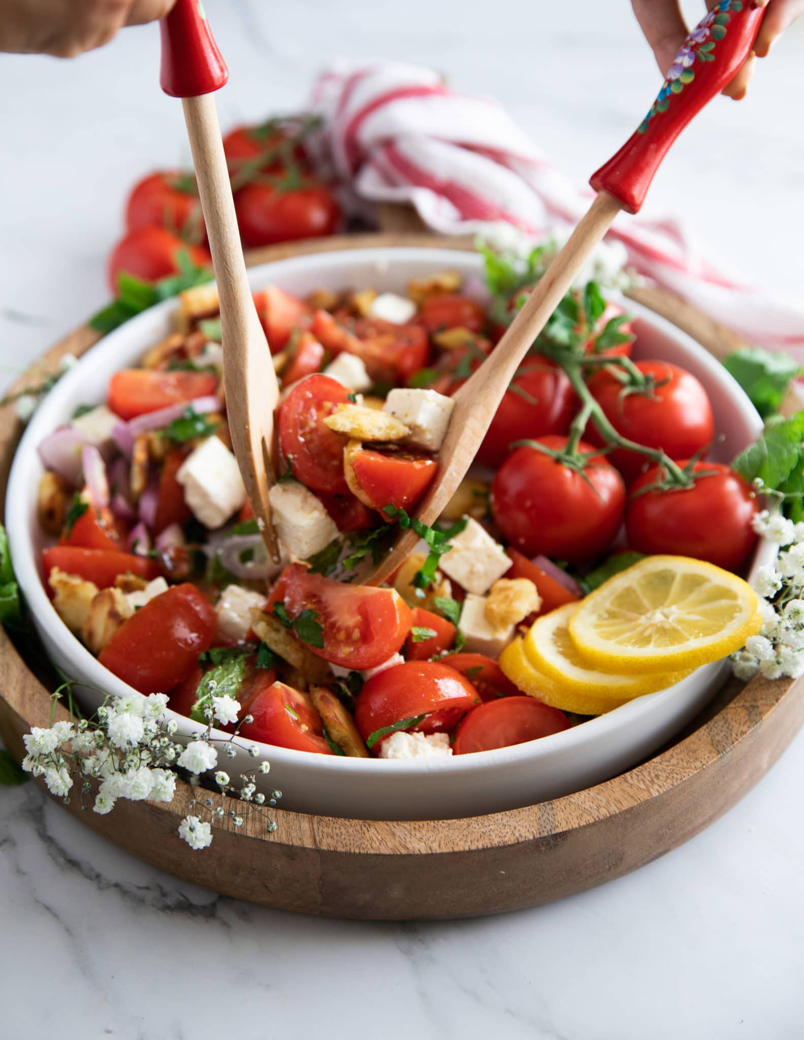 Salad spoons tossing the tomato salad with the simple dressing