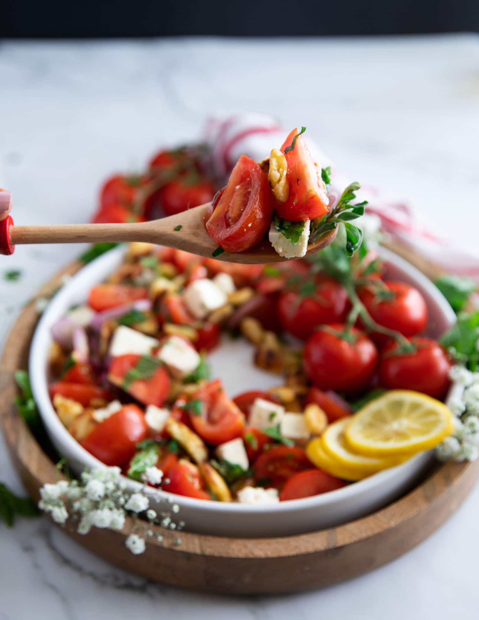 A salad serving spoon serving up some tomato salad showing how juicy the tomatoes are