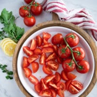 A large salad plate with fresh tomatoes quartered ready to assemble the tomato salad recipe