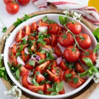 thinly sliced shallots and fresh herbs are added over the tomatoes
