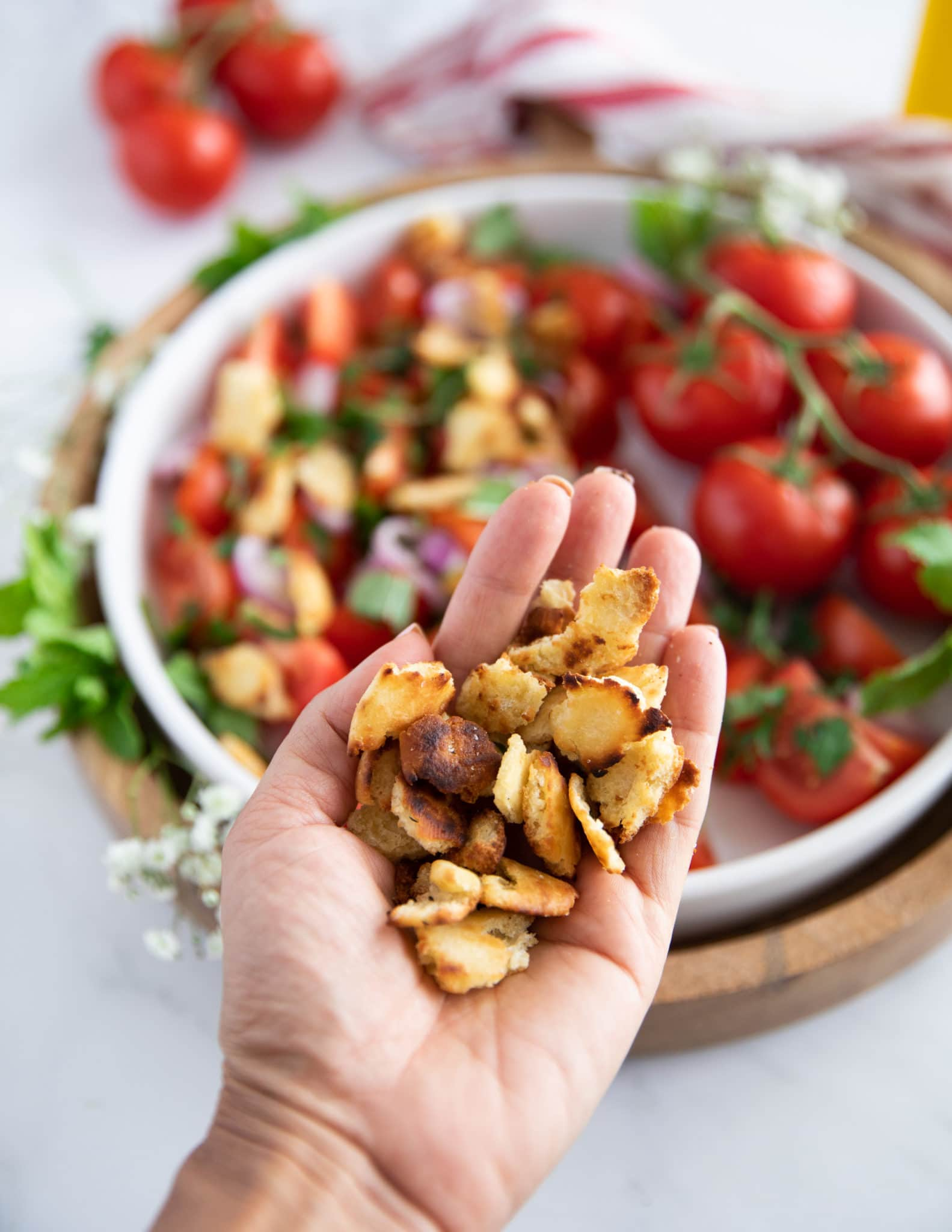 A hand holding the toasted bread chunks ready to toss into the salad