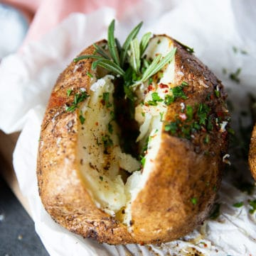 Close up of air fryer baked potato sliced and seasoned with a sprig of rosemary