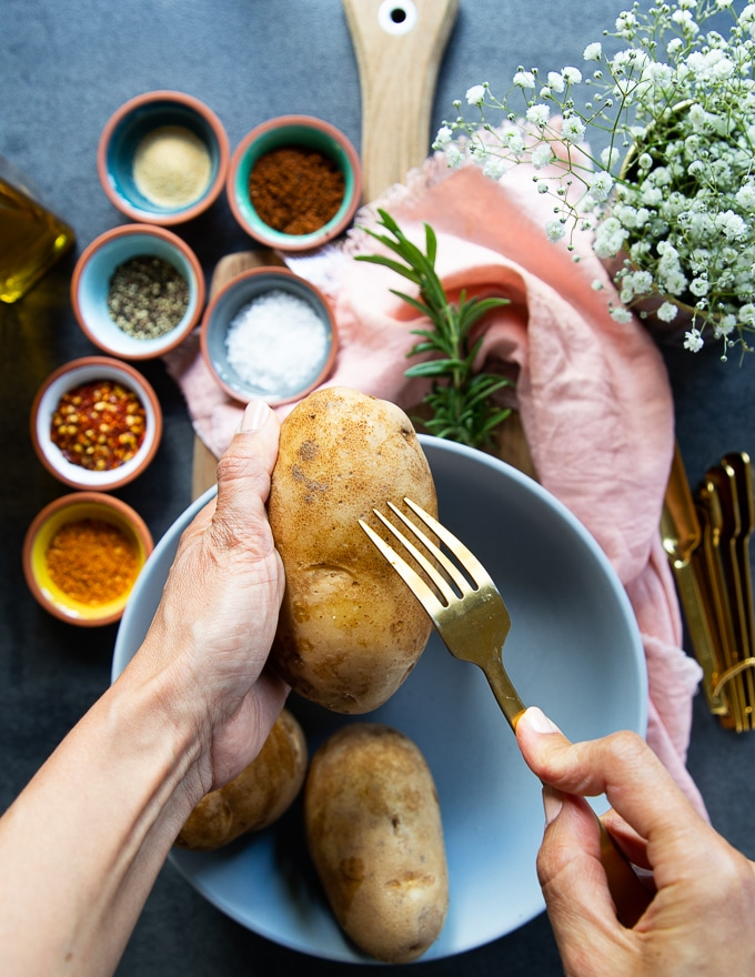A hand holding a Russet Potato and pricking it with a fork