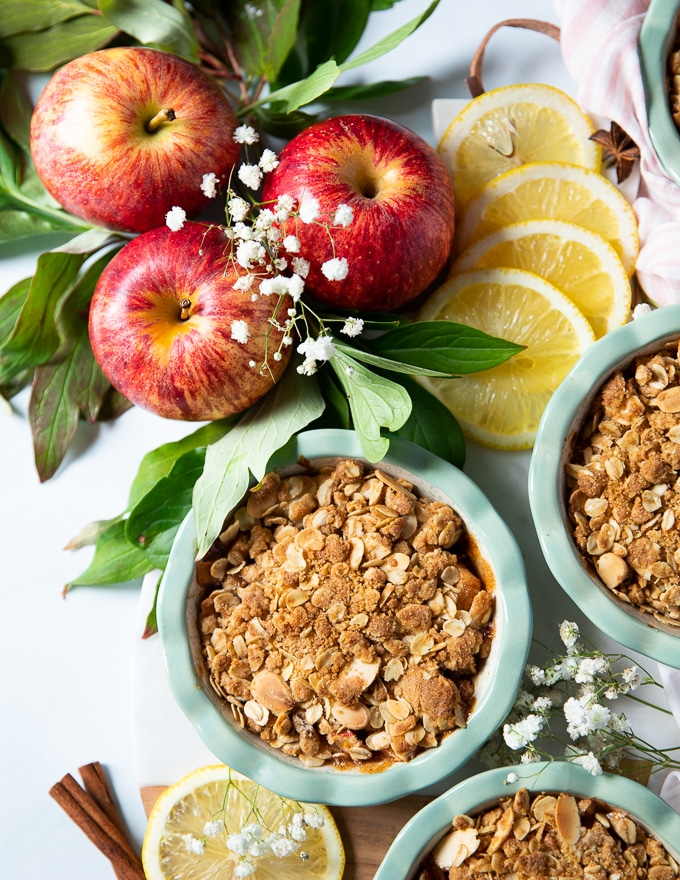 close up of a baked apple crumble showing the crisp crumble topping surrpunded by apples and lemon slices