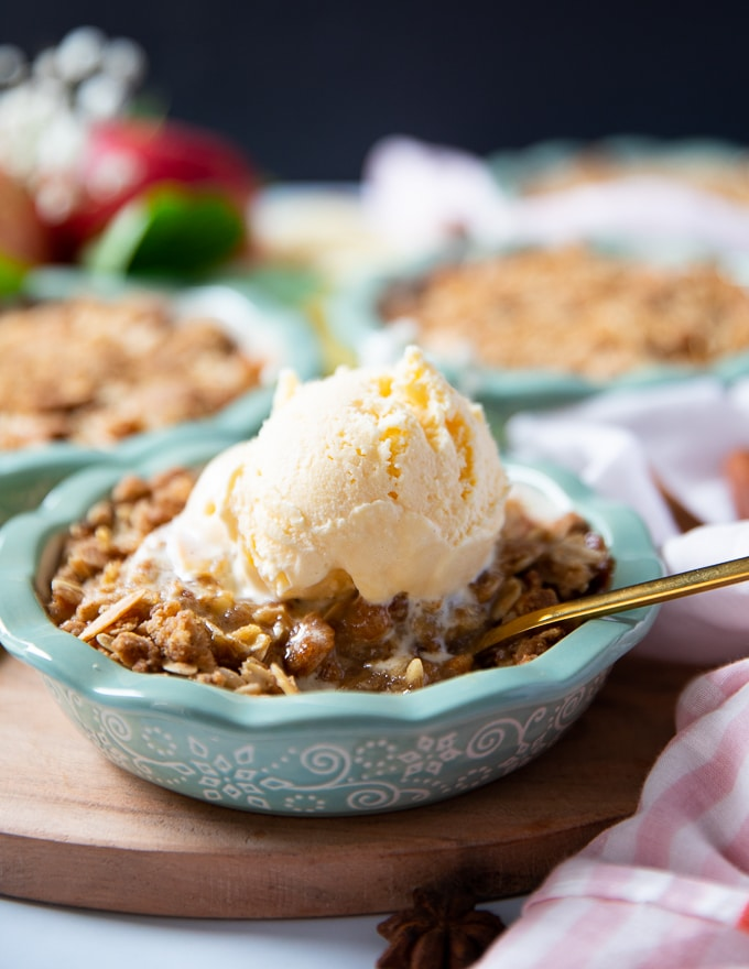 Apple crumble on a baking dish topped with vanilla ice cream and a spoon inside