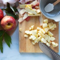 Apples being chopped on a cutting board, peeled and desseded