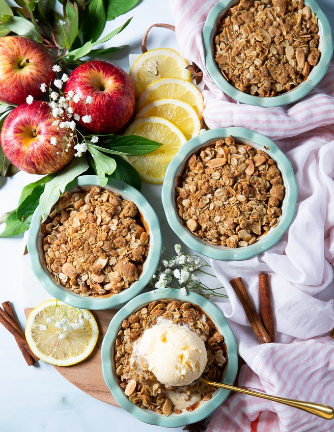 A set of four baked apple crumbles on a board surrounded by a spoon and vanilla ice cream on one of them, some apples, lemon slices and cinnamon sticks