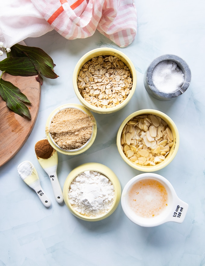 small bowls with ingredients for the apple crumble topping including butter , flour , sugar , oats , cinnamon and spices