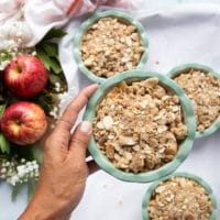 a hand holding the apple dessert topped with the crumble topping and ready to bake