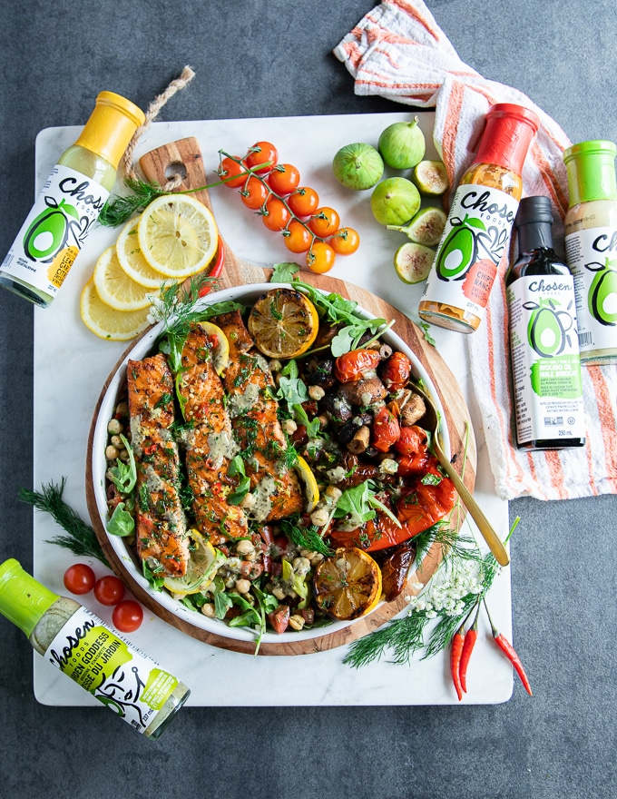 grilled salmon served on a plate surrounded by chickpea salad, some lemon slices, grilled veggies and a collection of dressings