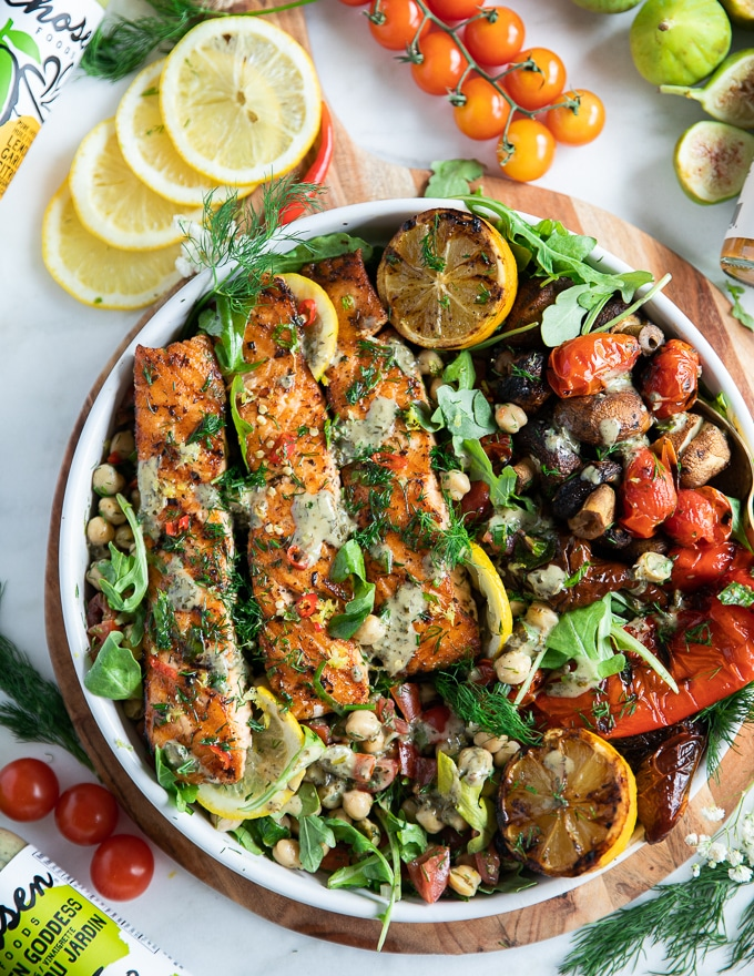 Grilled salmon on a plate with some grilled veggies, chickpea salad, surrounded by lemon slices