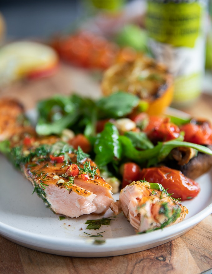 A piece of flaked grilled salmon on a plate showing how juicy and succulent the grilled salmon recipe is