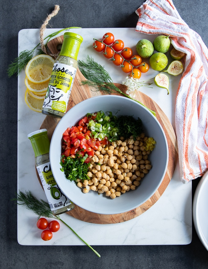 chickpea salad ingredients to serve with the grilled salmon recipe including a bowl of chickpeas, fresh herbs, tomatoes and green onions