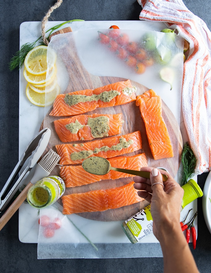 A hand drizzling the grilled salmon marinade over pieces of salmon fillets on a white marble