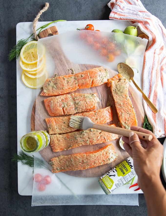 A hand brushing the salmon fillets with the grilled salmon marinade coating it well on both sides