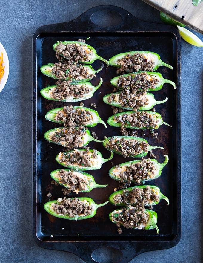 Jalapeño peppers on a baking sheet stuffed with the cheese mixture and topped with the spice lamb