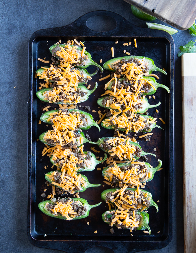 A final sprinkle of cheese is added over the stuffed jalapenos before going into the oven