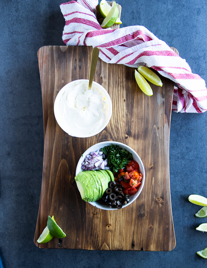 A colecyion of different nachos topping to sprinkle of the baked jalapenos including black olives, tomatoes, cilantro, onions, avocado and sour cream