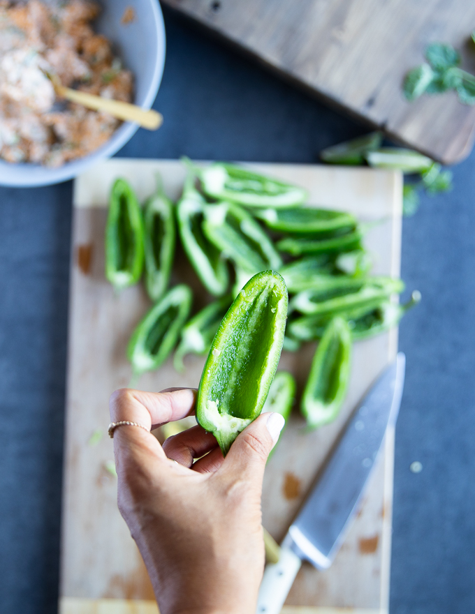 A handholding a jalapeño pepper cut in half, deseeded to remove the spice from it